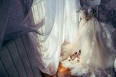 新娘室水平的时兴的长的婚礼礼服开花垂悬椅子窗口阳光的米黄高跟鞋 免版税库存图片