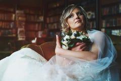 新娘对她花束坐负周道在一把老大椅子 库存照片