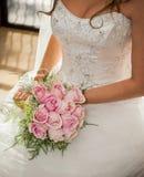 新娘开会,献桃红色玫瑰她的大花束在她的膝部 免版税库存照片