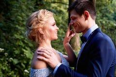 新娘开玩笑地看新郎 并且接触手指对他的鼻子技巧  婚姻的步行和照片写真 库存照片
