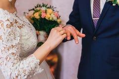 新娘戴着在新郎` s手指的一只金戒指在婚礼 图库摄影