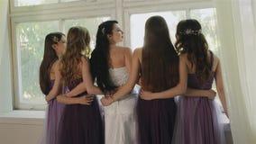 新娘拥抱与女傧相在演播室 紫色礼服的美丽的女孩嘲笑窗口 妇女摆在 影视素材