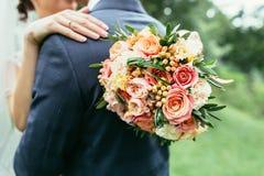新娘拿着婚礼花束的和婚礼的拥抱新郎 免版税库存图片