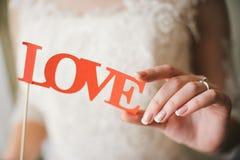 新娘拿着词爱的手中纸信件 免版税库存图片