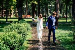 新娘新郎公园走 在爱的夫妇婚礼之日 免版税库存图片