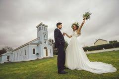 新娘新郎花微笑摆在花的婚礼 库存图片