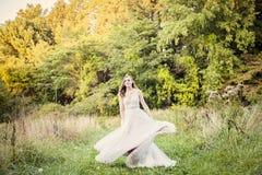 新娘旋转的婚礼礼服在森林里 免版税库存图片