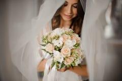 新娘早晨准备 一个可爱的新娘的画象白色面纱的与婚礼花束 免版税图库摄影