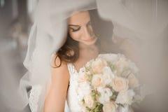 新娘早晨准备 白色面纱的可爱的新娘与婚礼花束 免版税图库摄影