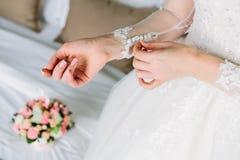 新娘是紧固在她的礼服的袖子,为婚礼之日做准备 免版税图库摄影