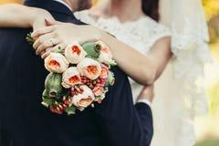 新娘有婚礼花束的拥抱新郎 免版税库存照片