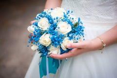 新娘有蓝色花束的` s手  免版税库存照片