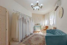 新娘沙龙内部  在的美丽的婚礼礼服挂衣架 库存照片