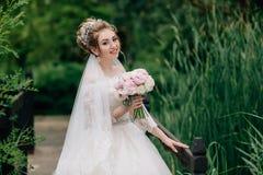 新娘沿在河的桥梁走 女孩在婚礼礼服和牡丹花束摆在  库存照片