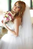 新娘混合她的头发并且拿着在她的胳膊的婚礼花束 库存照片