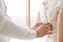新娘白色鞋带婚纱 在婚纱投入的新娘帮助 免版税库存照片