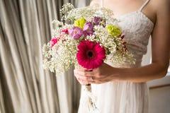 新娘的中央部位在家拿着花束的婚礼礼服的 图库摄影