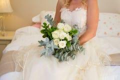 新娘的中央部位拿着花束的婚礼礼服的,当坐床时 库存图片