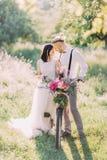 新娘的可爱的照片运载自行车的婚礼白色礼服和现代穿戴的新郎的在中间 免版税库存照片