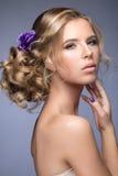 新娘的图象的美丽的白肤金发的女孩有紫色花的在她的头 秀丽表面 免版税库存图片