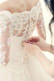 新娘的女朋友帮助穿戴束腰 图库摄影