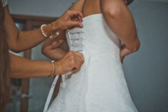 新娘的女朋友帮助穿戴礼服1914年 免版税库存照片