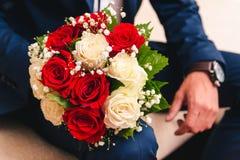 新娘的婚姻的花束从白色和米黄玫瑰到新郎的手 免版税库存照片