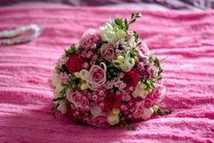 新娘的婚礼花束在床上 免版税图库摄影
