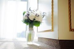 新娘的婚礼花 拿着五颜六色的花束替换者的妇女在窗口附近,在天 免版税图库摄影