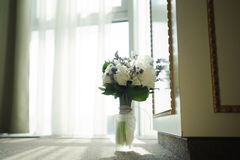 新娘的婚礼花 拿着五颜六色的花束替换者的妇女在窗口附近,在天 免版税库存照片