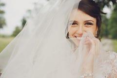 新娘的微笑闪闪发光,当她掩藏它在面纱后时 库存照片