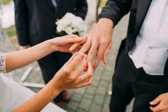 新娘的手的特写镜头视图把婚戒放的在新郎的手指上 免版税库存照片