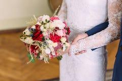新娘的手的特写镜头视图拿着玫瑰和不同的草本的colouful花束  库存照片