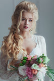 新娘的早晨 停留在与花束的窗口附近的白色便服的美丽的少妇 库存照片