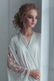 新娘的早晨 典雅的白色长袍的美丽的少妇有时尚站立在附近的婚礼发型的 库存照片