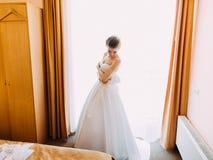 新娘的水平的侧视图长的白色婚礼礼服的在屋子里 免版税库存照片