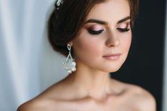 新娘的特写镜头画象有金刚石耳环、婚姻的构成和发型的在一个黑暗的演播室摆在 美丽的年轻人 免版税库存图片