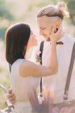 新娘的特写镜头画象白色婚礼礼服的在晴朗的春天的宠爱现代穿戴的新郎 免版税库存照片