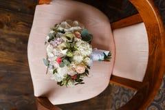 新娘的甜花束一把减速火箭的椅子的 免版税库存图片
