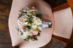 新娘的甜花束一把减速火箭的椅子的 库存图片