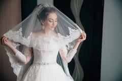 新娘的画象鞋带婚礼礼服和长的面纱的 女孩看她的成套装备,她的头发装饰与 库存照片