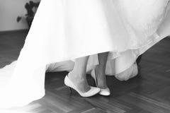 新娘的腿特写镜头在白色婚礼鞋子的 免版税库存照片