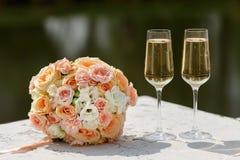 新娘的花束和两块香槟玻璃 库存照片
