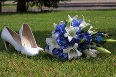 新娘的花束和鞋子绿草的 免版税库存图片