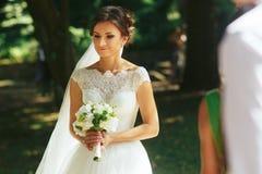 新娘看起来周道的藏品在她的胳膊的花束 图库摄影