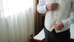 年轻新娘礼服和衬衫纽扣 愉快的年轻人新郎在他们的婚礼之日 按他的在窗口前面的人衬衣 股票视频