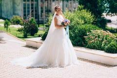 新娘穿一件弯曲的礼服并且走与沿美丽如画的大道的长的面纱 与花束的婚姻的步行 库存图片