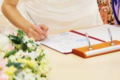 新娘签署的结婚证书或合同 免版税库存图片