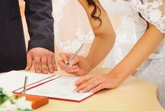 新娘签署的结婚证书或婚姻的合同 免版税图库摄影