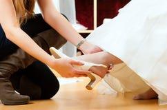 新娘给女装店婚礼穿衣 免版税库存照片